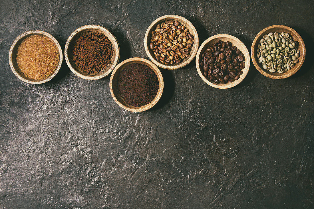 Variety of grounded, instant coffee, different coffee beans, brown sugar in wooden bowls in row over dark texture background
