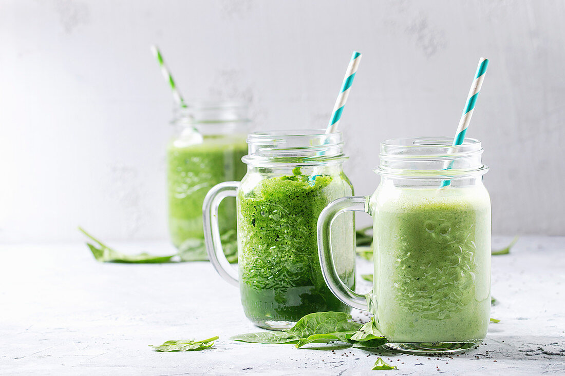 Variety of three color green spinach kale apple yogurt smoothie in mason jars with retro cocktail tubes over gray background