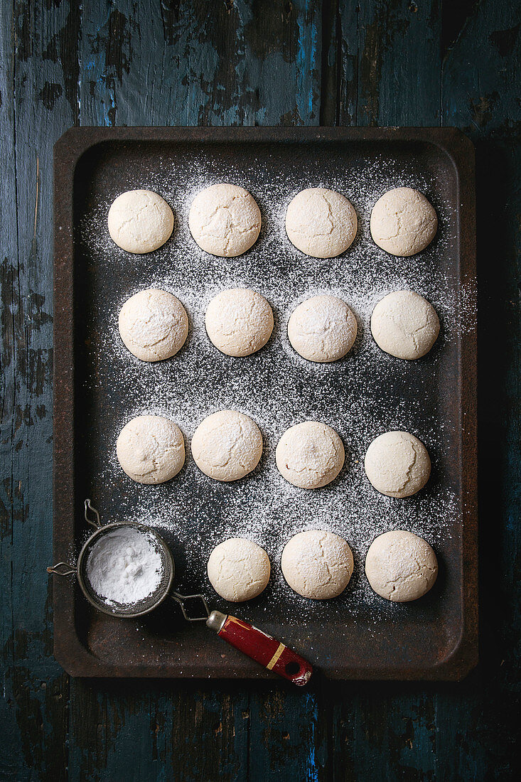 Homemade almond cookies with sugar powder, with vintage sieve, on old oven tray over dark blue wooden table