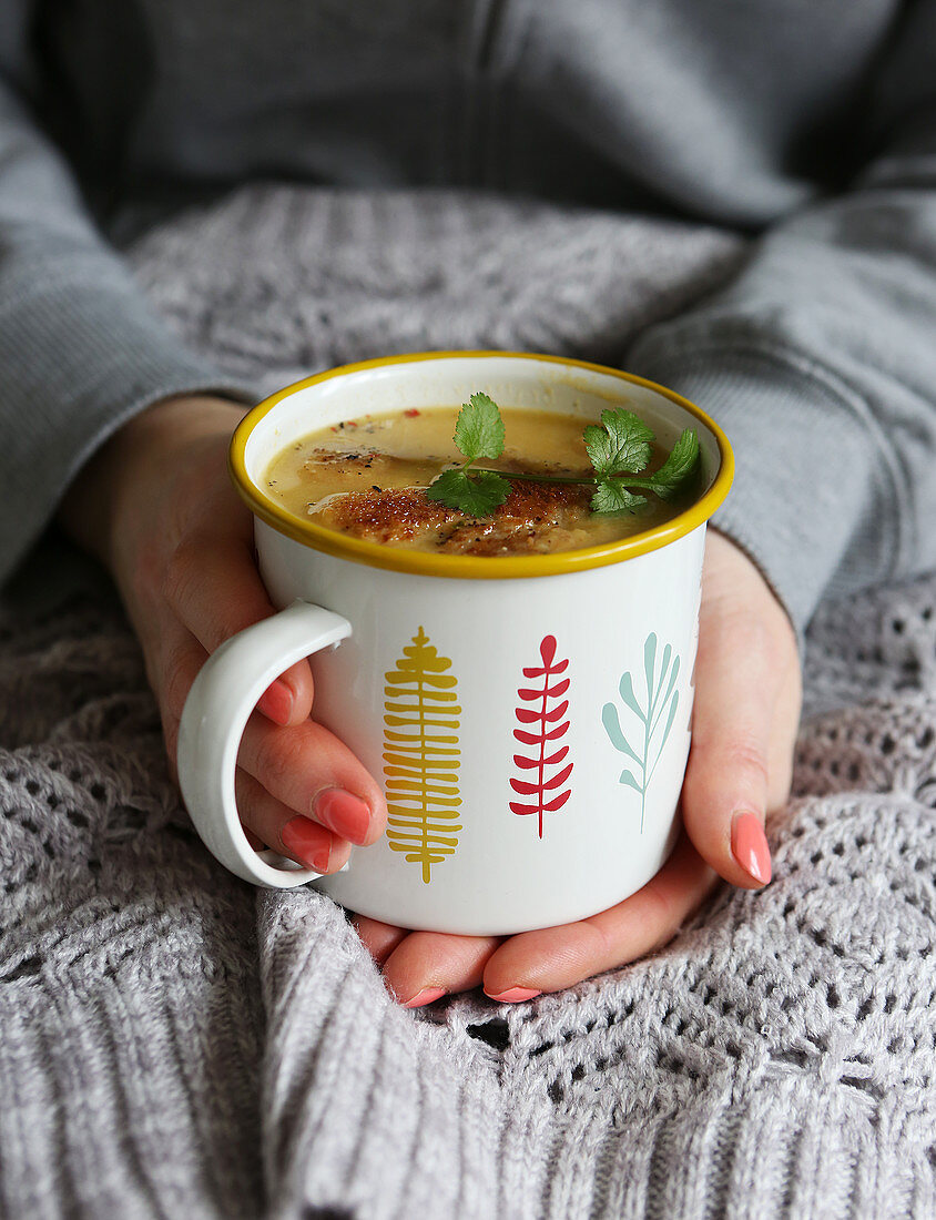 Vegetable soup in mug topped with croutons and fresh coriander