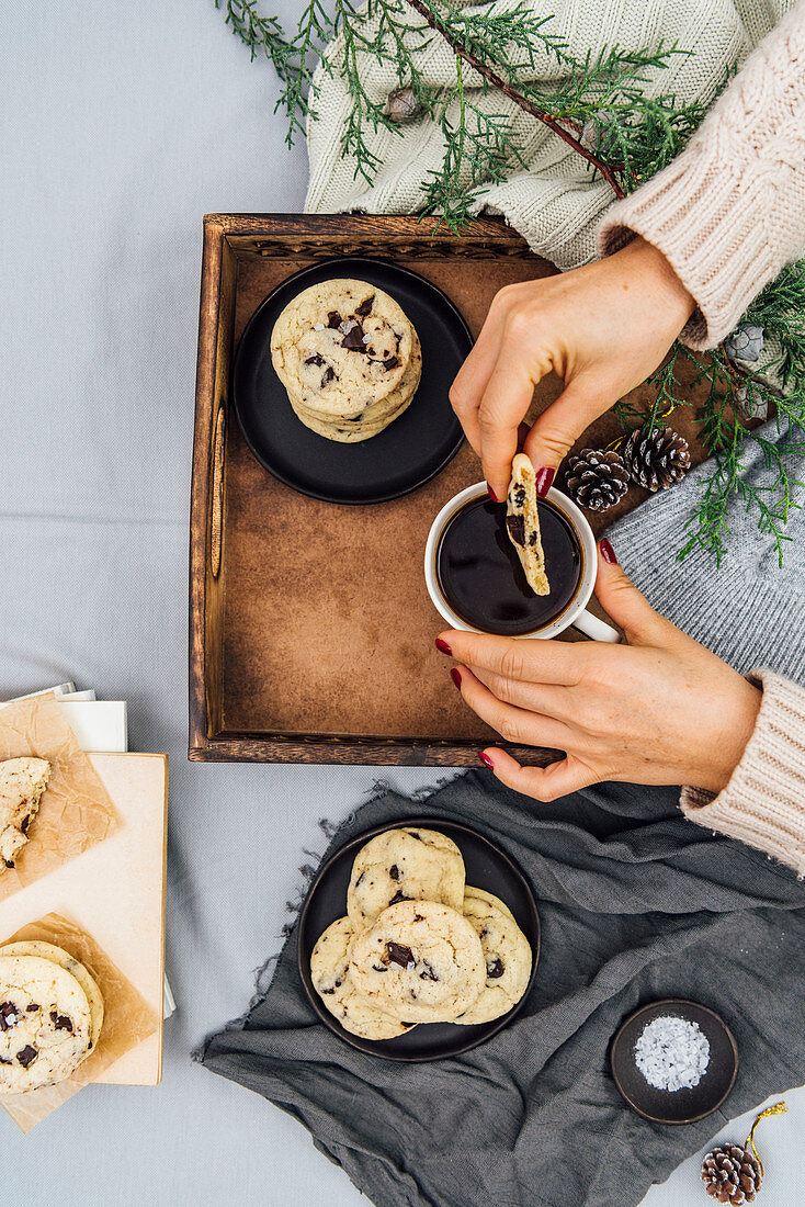 A woman dipping a chocolate chip cookie into her coffee in a wooden tray