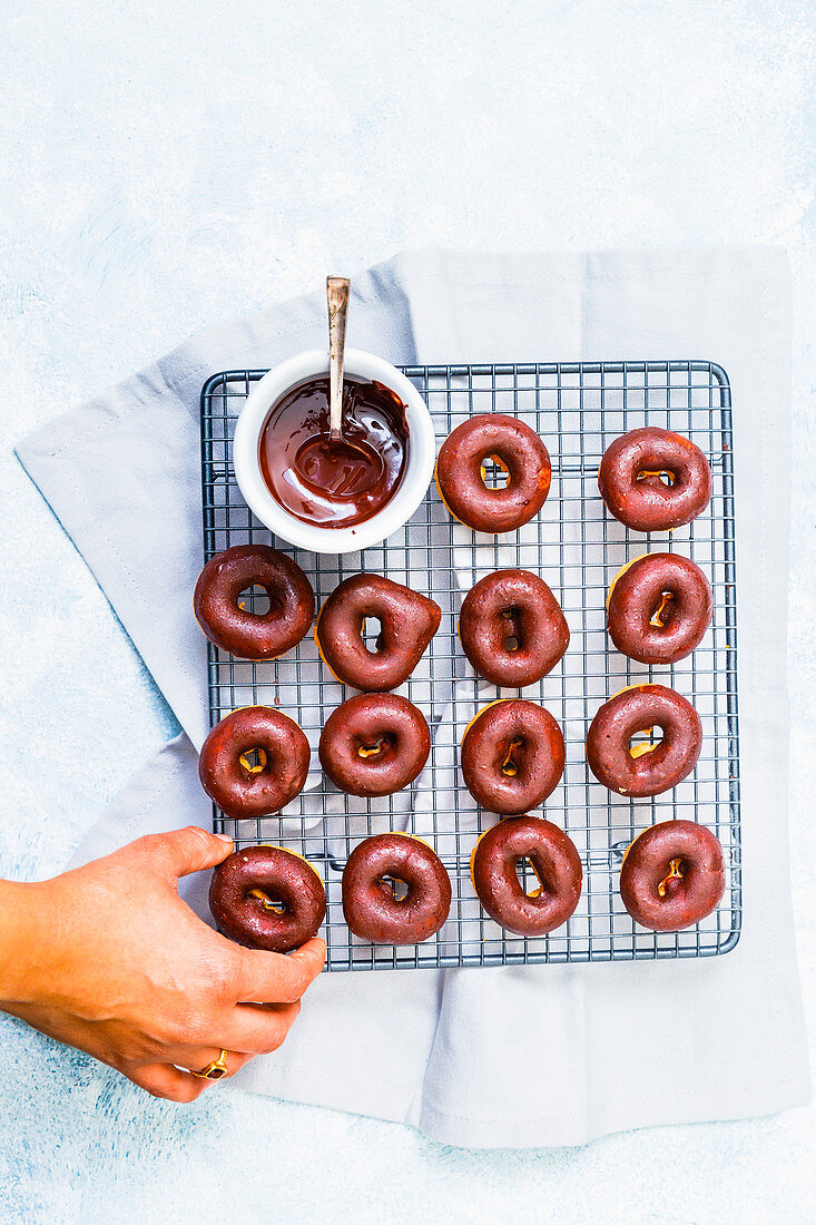 Lady picking a Homemade Mini Chocolate Glazed Doughnut from the cooling rack