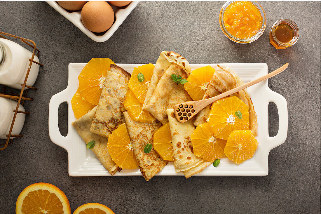 Crepes suzette with cream cheese filling, orange sauce and fresh oranges