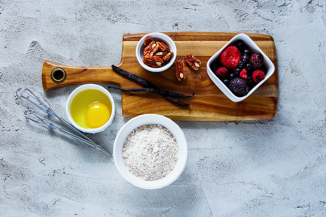 Wooden cutting board with ingredients for baking (whole flour, egg, frozen berries, nuts and vanilla) over concrete textured background
