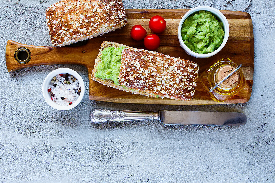 Wooden cutting board with homemade delicious avocado sandwiches over concrete textured background
