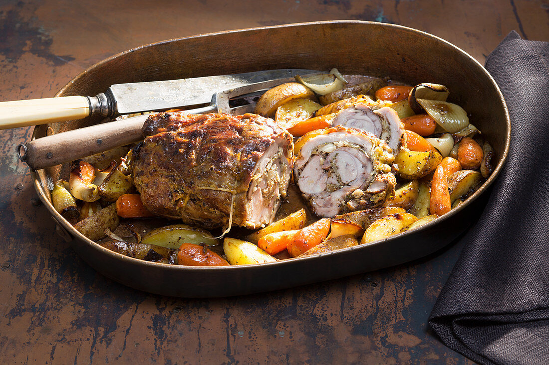 Oven-roasted stuffed shoulder of goat on a bed of colourful vegetables