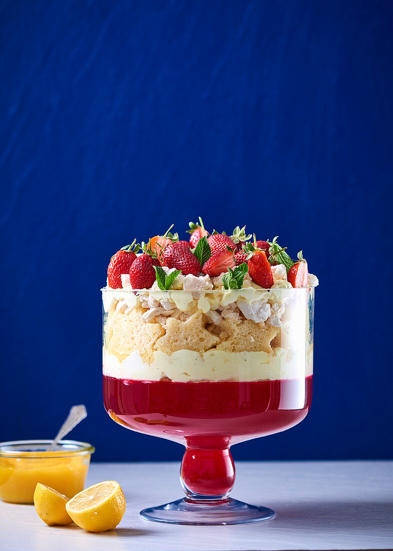 Trifle with strawberry jelly, biscuit stars, strawberries and lemon curd