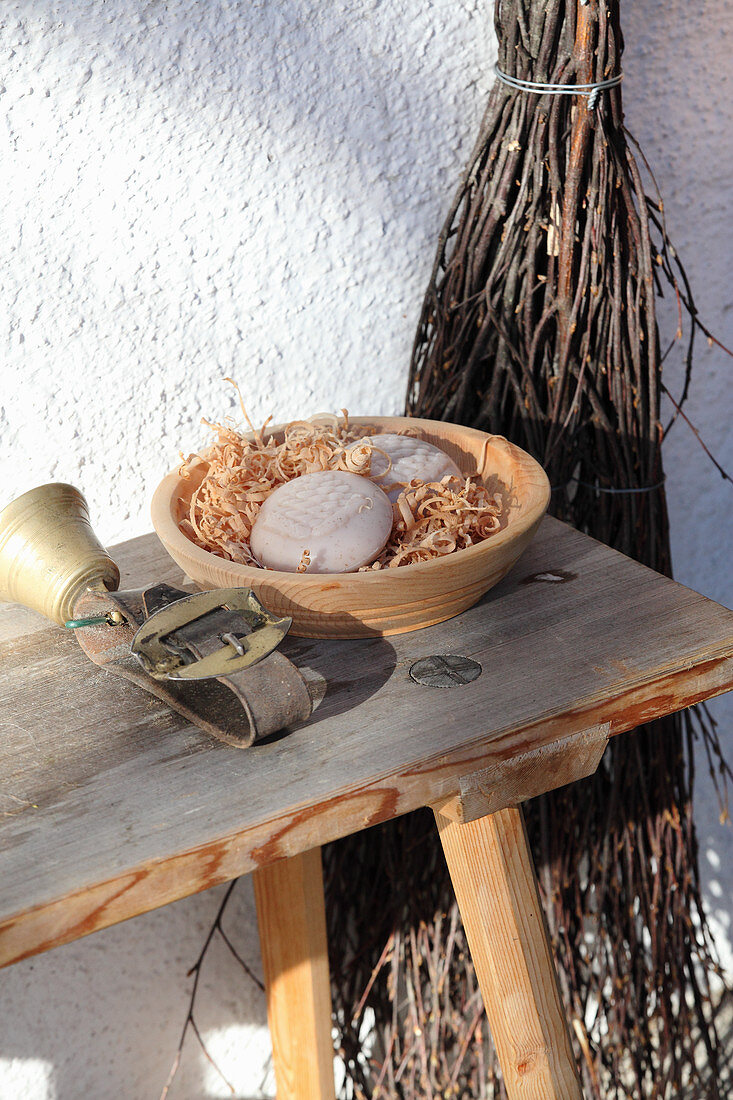 A sheep bell and bars of soap in a terracotta bowl on a wooden bench