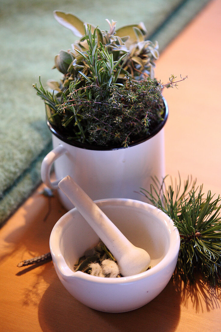 Fresh herbs in an enamel cup, and a mortar with herbs and sheep's wool