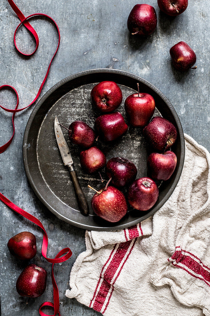Red apples on a metal tray with a knife