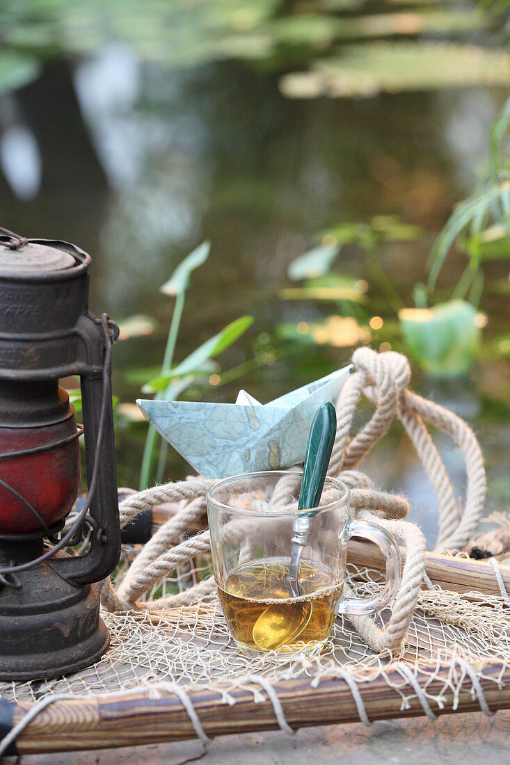 Herbal tea against nausea in a glass cup by a pond
