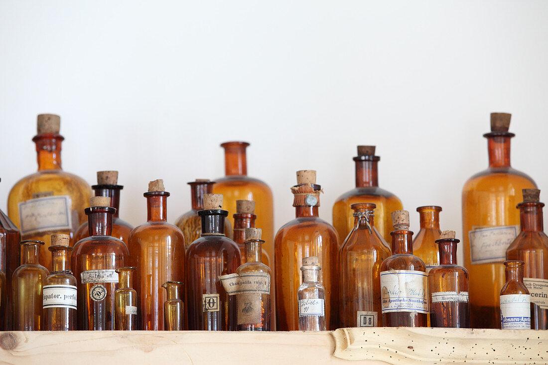 Apothecary bottles on wooden shelf
