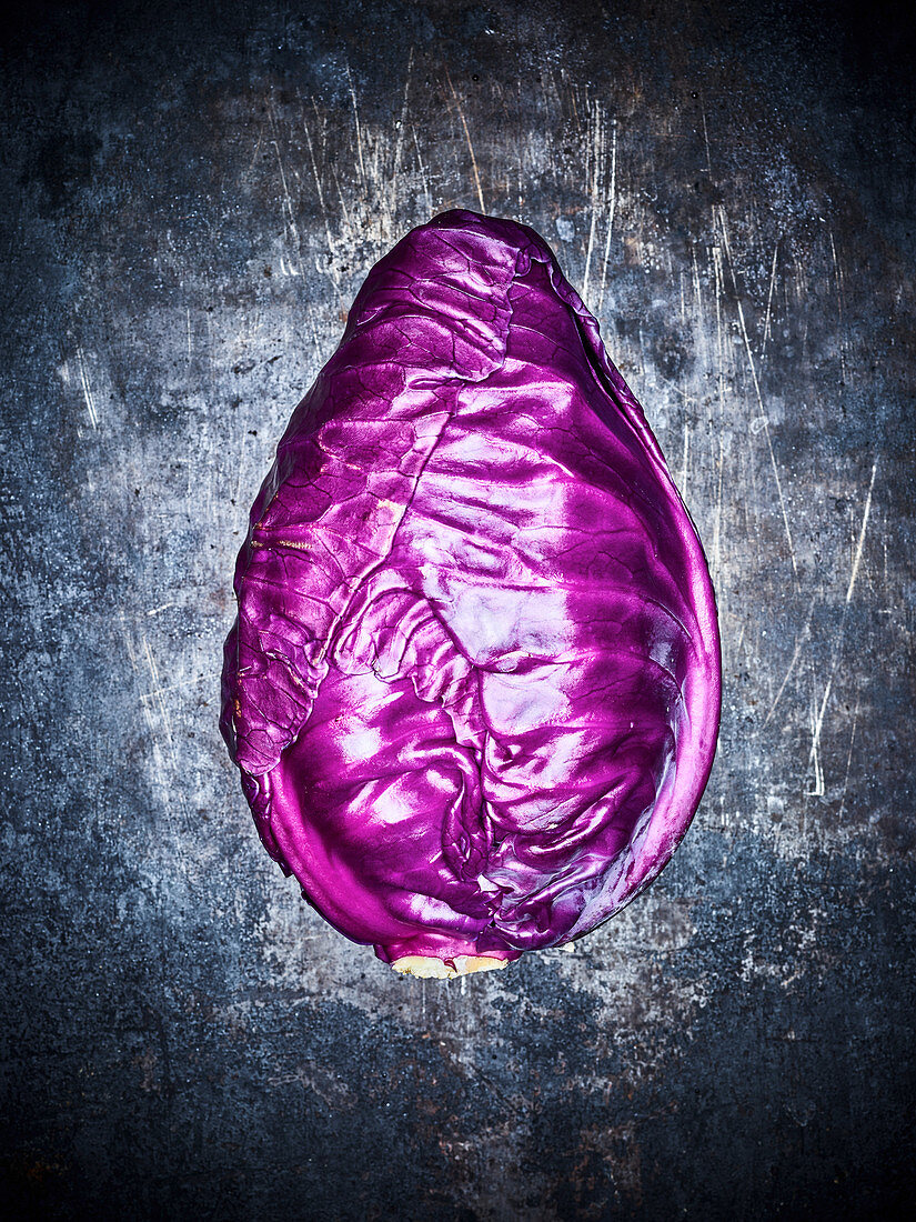 A red cabbage on a dark metal background (top view)