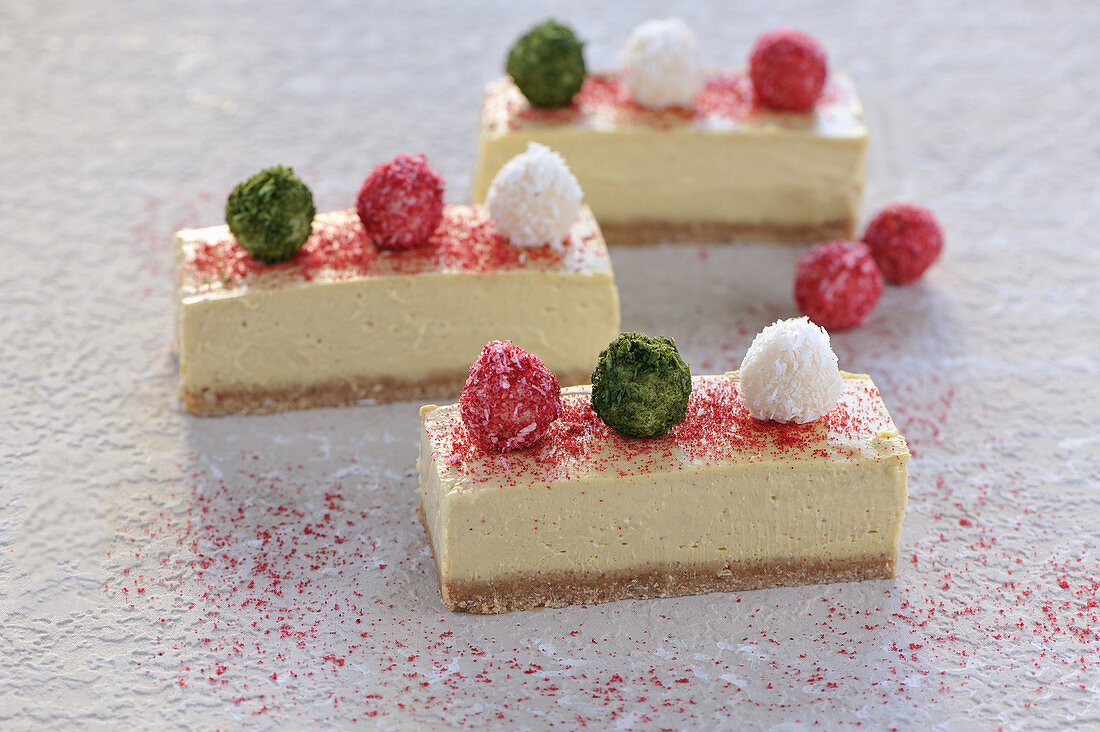 Raw mango and coconut cheesecake slices decorated with raspberry powder and coconut balls (vegan)