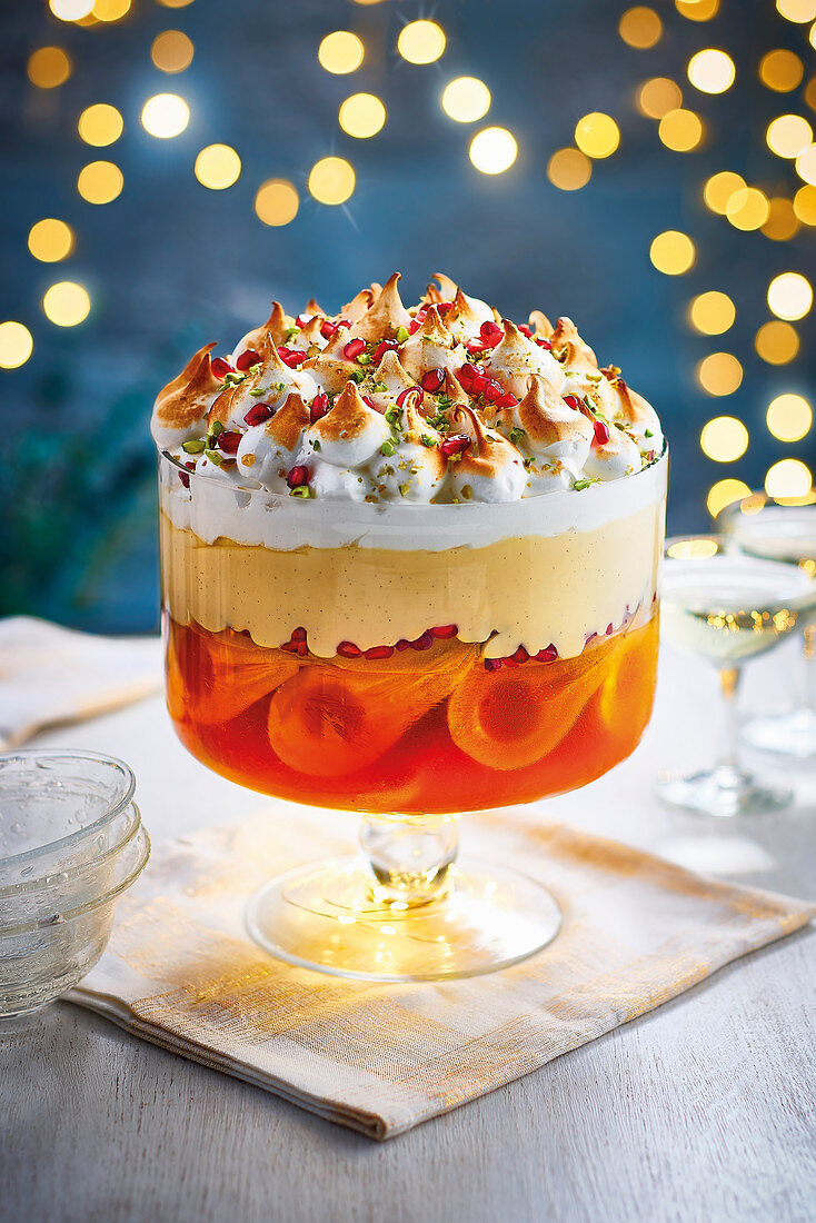 Boozy poached pear and pomegranate trifle with a saffron jelly set on a beed of sweet amaretti biscuits with a creamy vanilla custart and topped with a torched italian meringue pistachios and pomegranate seeds
