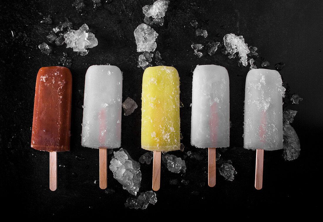Various popsicles: cola, lemon, and vanilla