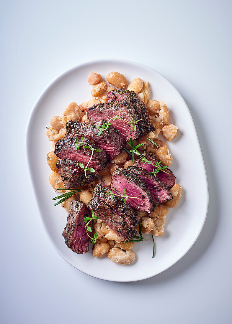Ostrich steaks on lima beans with garlic and rosemary