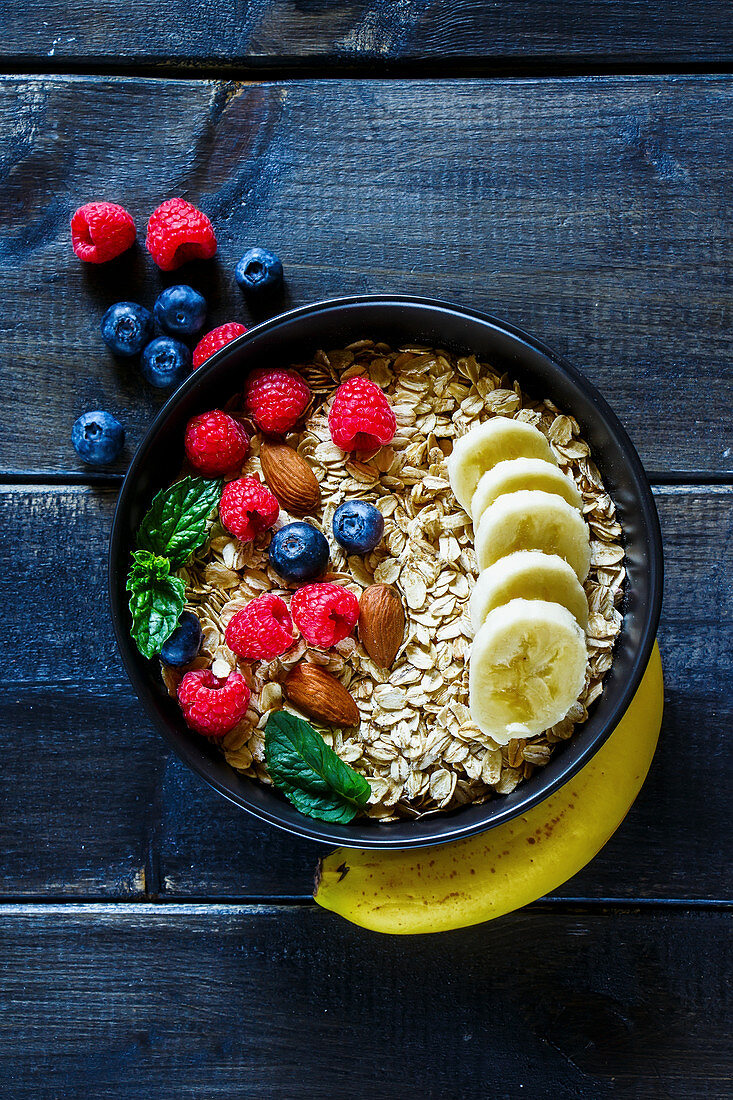 Oatmeal with berries, almonds and bananas in a bowl (top view)