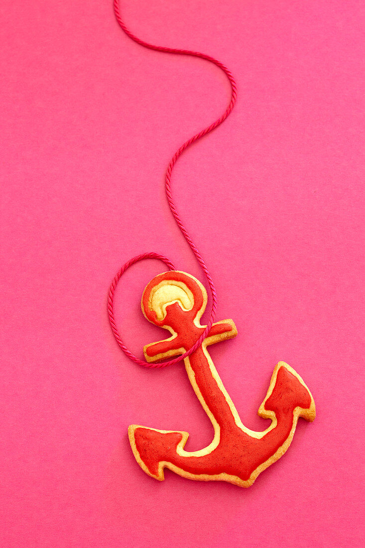 An anchor-shaped biscuit with red icing against a pink background