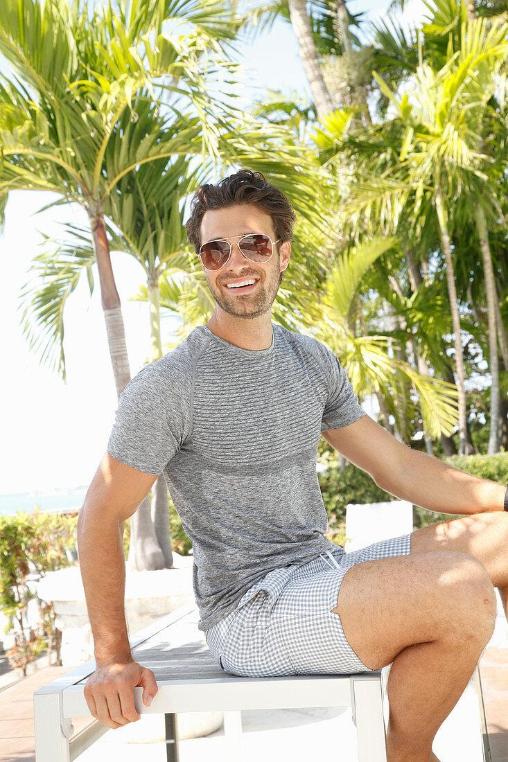 Junger Mann mit Sonnenbrille in grauem T-Shirt und Shorts