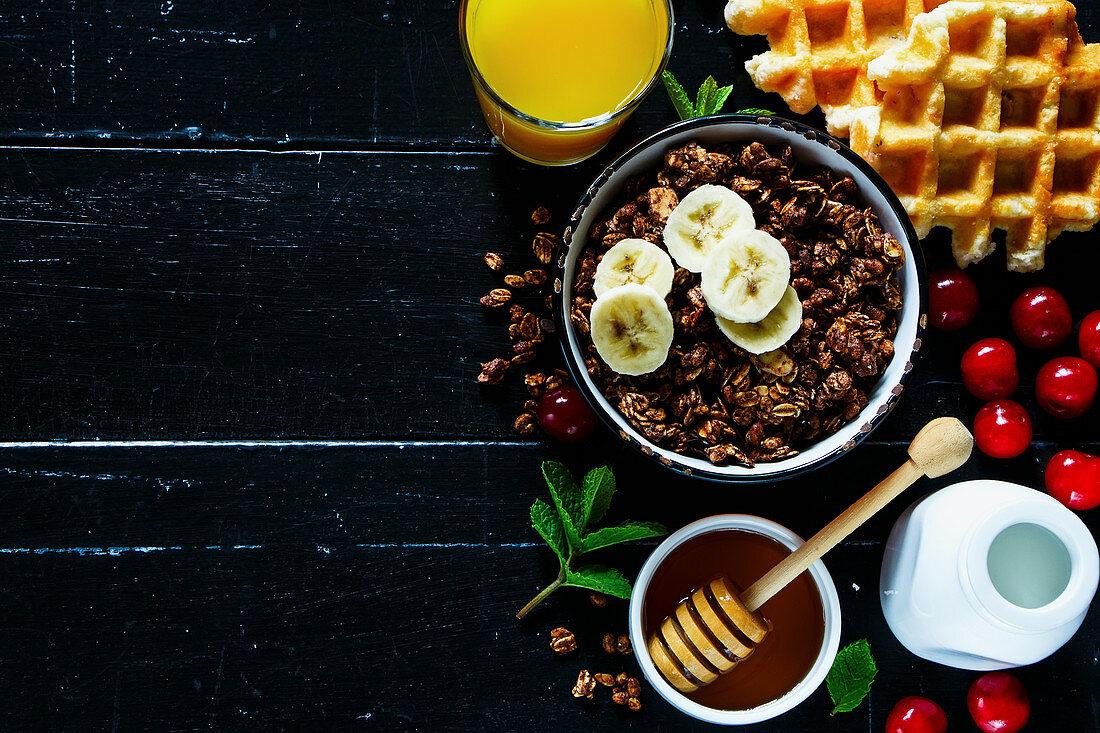 Bowl of chocolate oat granola, waffle, orange juice, fresh cherries, honey, mint and milk or yogurt bottle