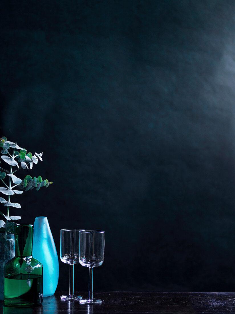 wine glasses, blue vase, green glass carafe
