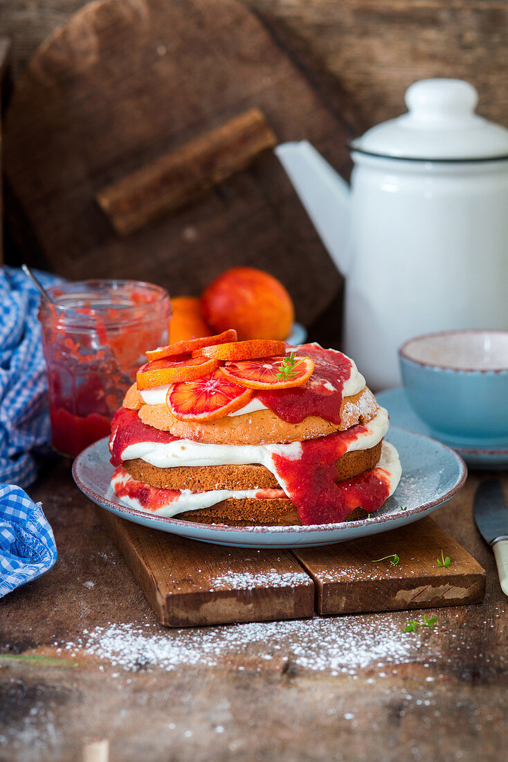 A small sponge cake with blood oranges and cream