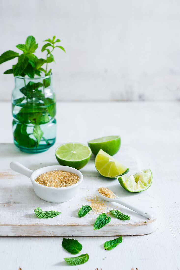 Some lime wedges, mint leaves and a small bowl and spoon with brown sugar