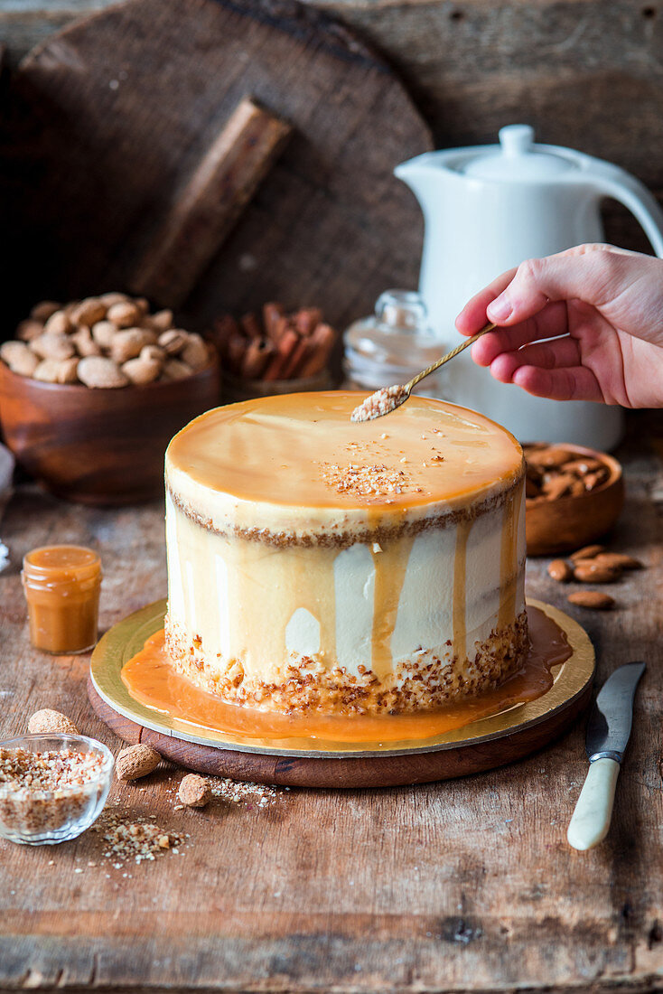 Pumpkin caramel cake with a hand sprinkling almonds