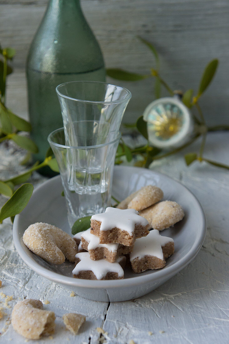 Cinnamon stars, vanilla crescent biscuits and shot glasses on a plate