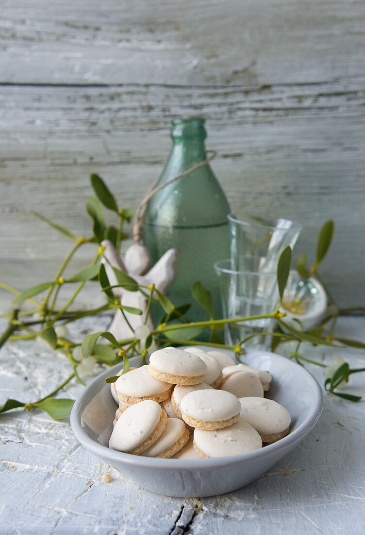A bowl of anise biscuits with shot glasses, a green bottle and an angel figurine in the background