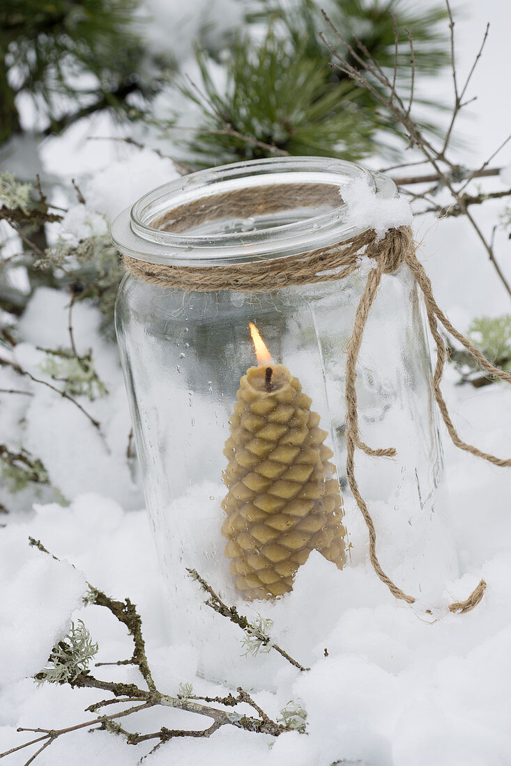 Pinecone-shaped beeswax candle in jar in snow