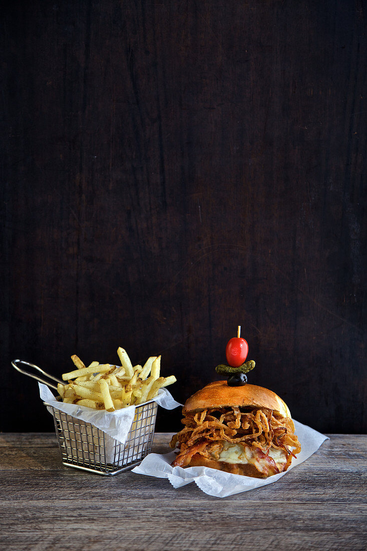Burger with cheese, bacon fried onions and french fries in a frying basket