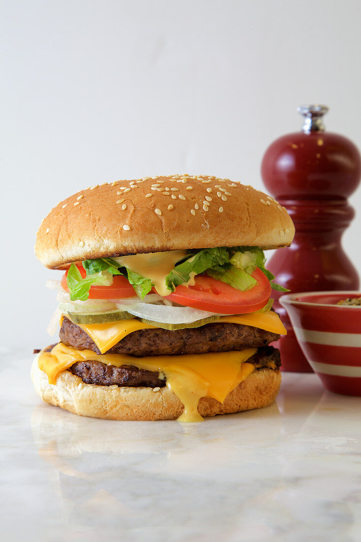 Double Burger with american cheese, lettuce and tomato on a white background, with extra spices