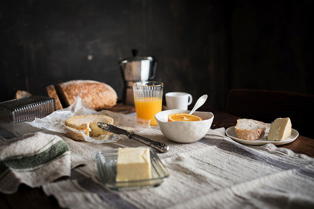 Coffee, orange juice, bread, butter and cheese on a breakfast table