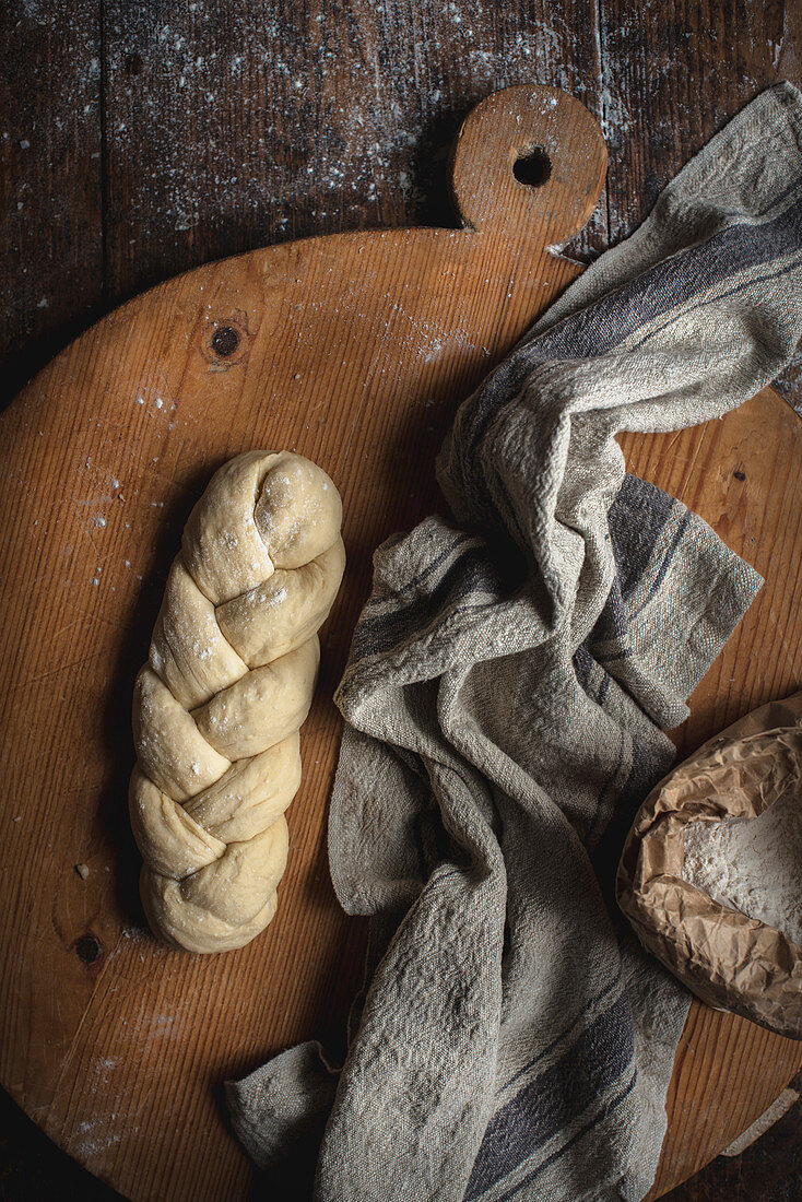 Unbaked challah bread (Jewish cuisine) on a wooden board