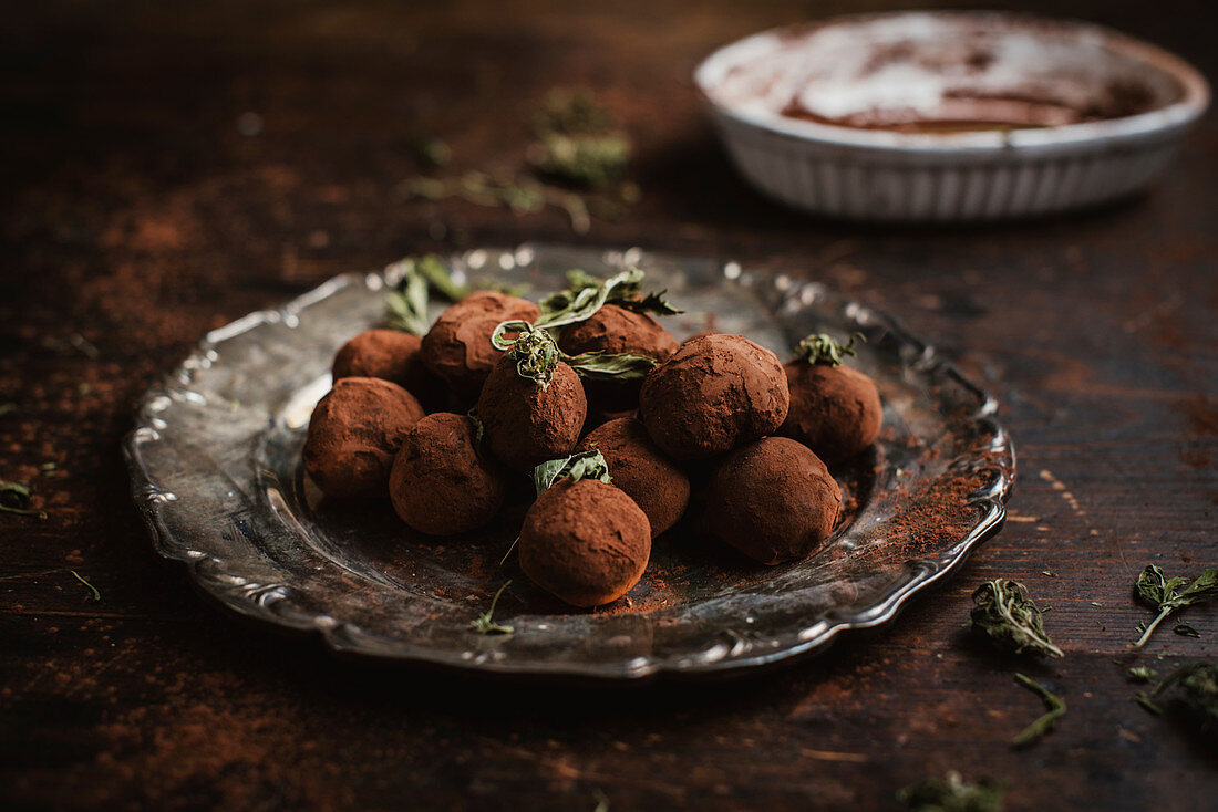 Home-made chocolate truffles with hemp oil on a silver plate