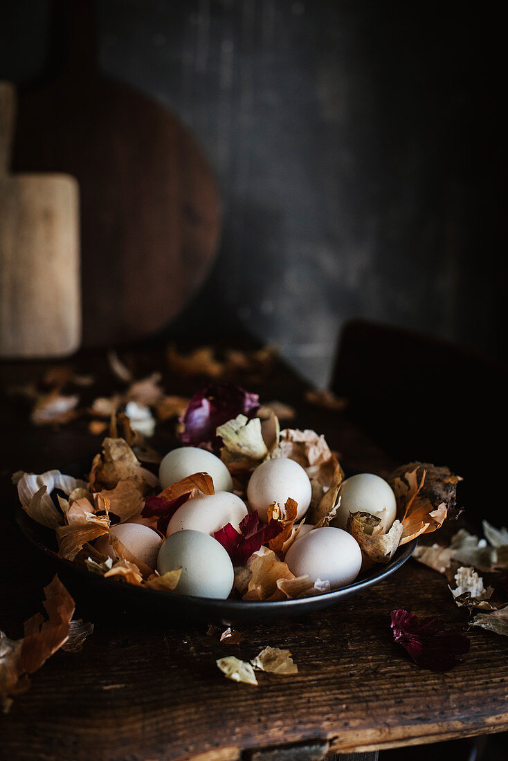 Naturally dyed eggs sitting on a plate amongst onion skins