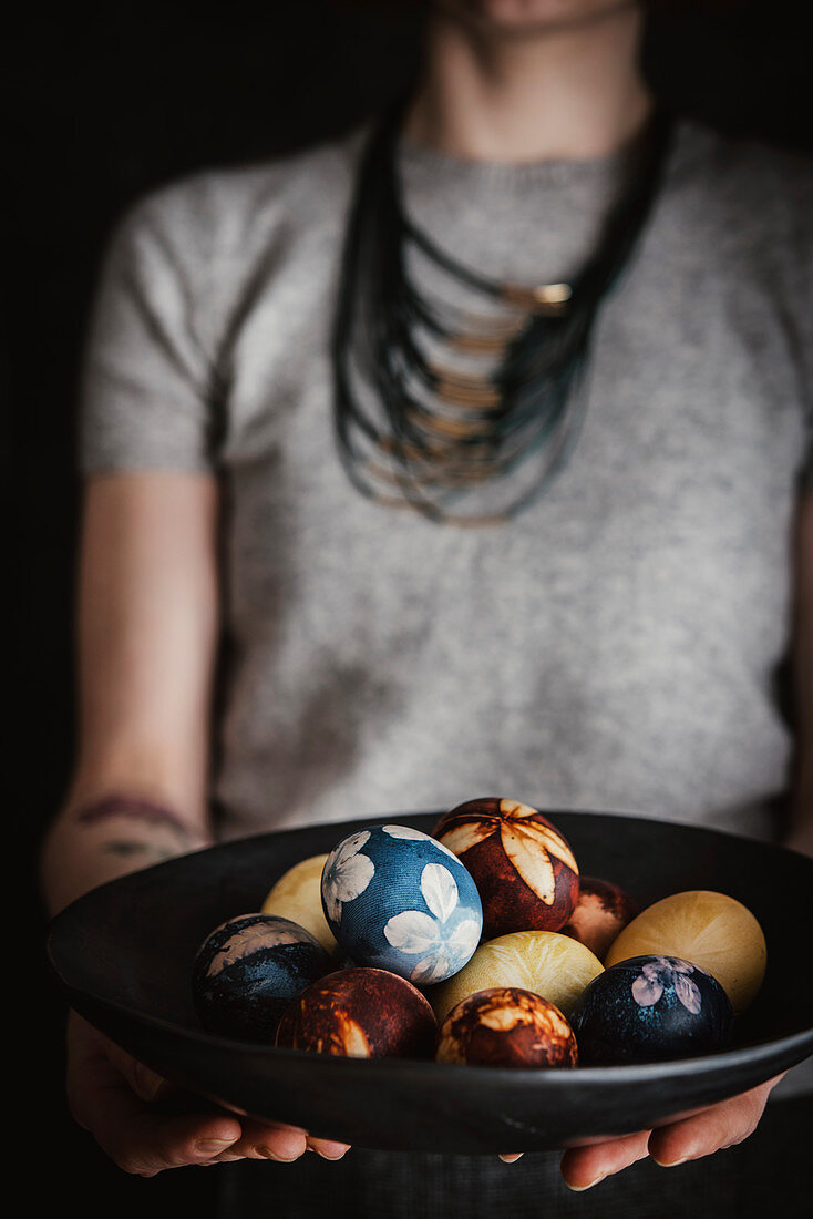 A woman holding a bowl of naturally dyed Easter eggs