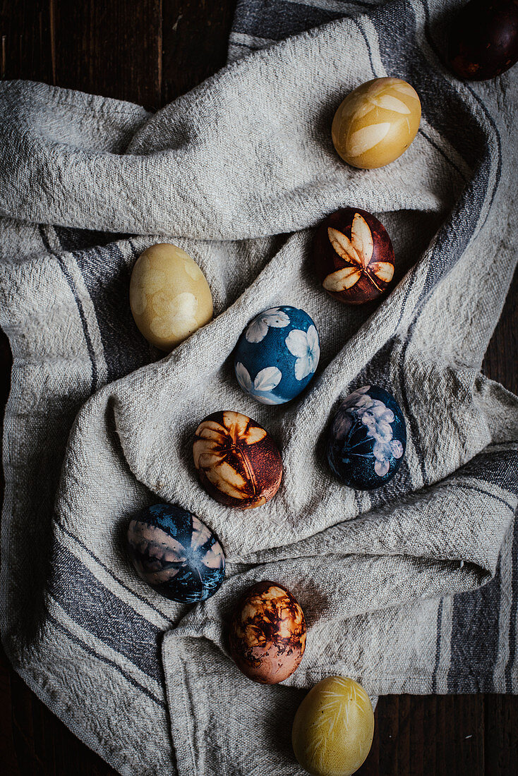 Naturally dyed eggs decorated with flowers on a linen cloth