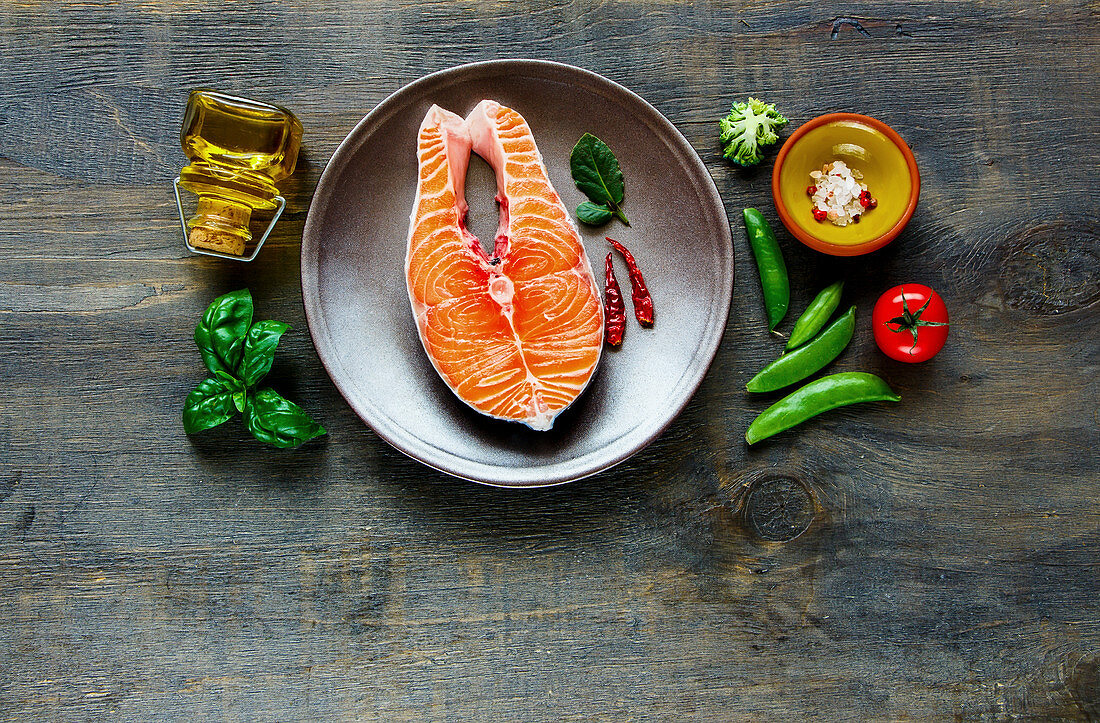 Raw salmon steak on a plate next to ingredients (seen from above)