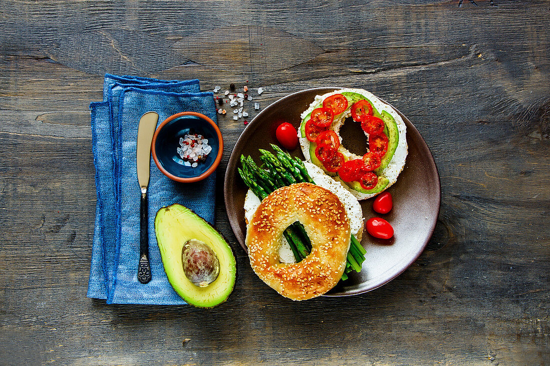 A vegetarian bagel topped with cream cheese, asparagus, avocado and tomatoes