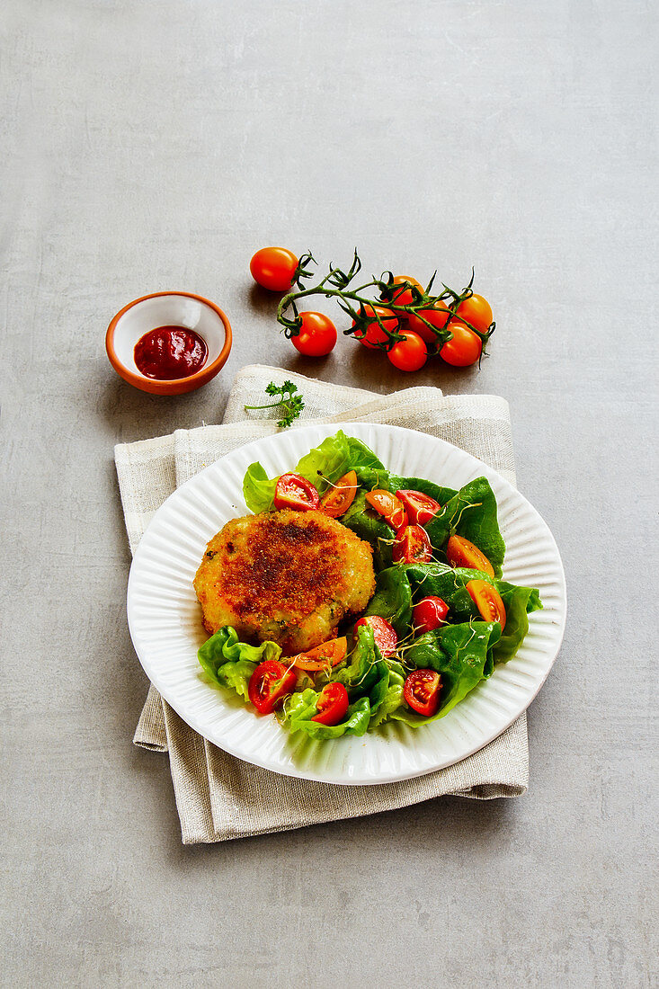 Vegan vegetable fritters with a mixed leaf salad and tomatoes