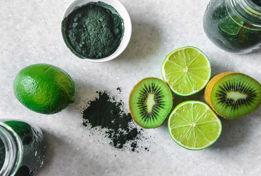 Halved kiwi and lime fruits, powdered spirulina, green smoothie in glass jars