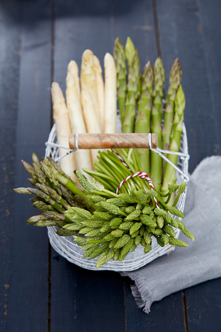 Various types of asparagus in a wire basket