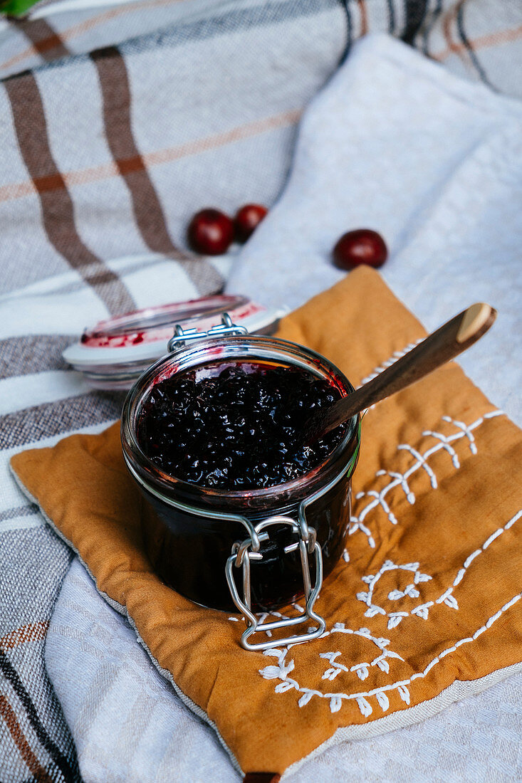 Jam in a glass jar on a fabric pillow