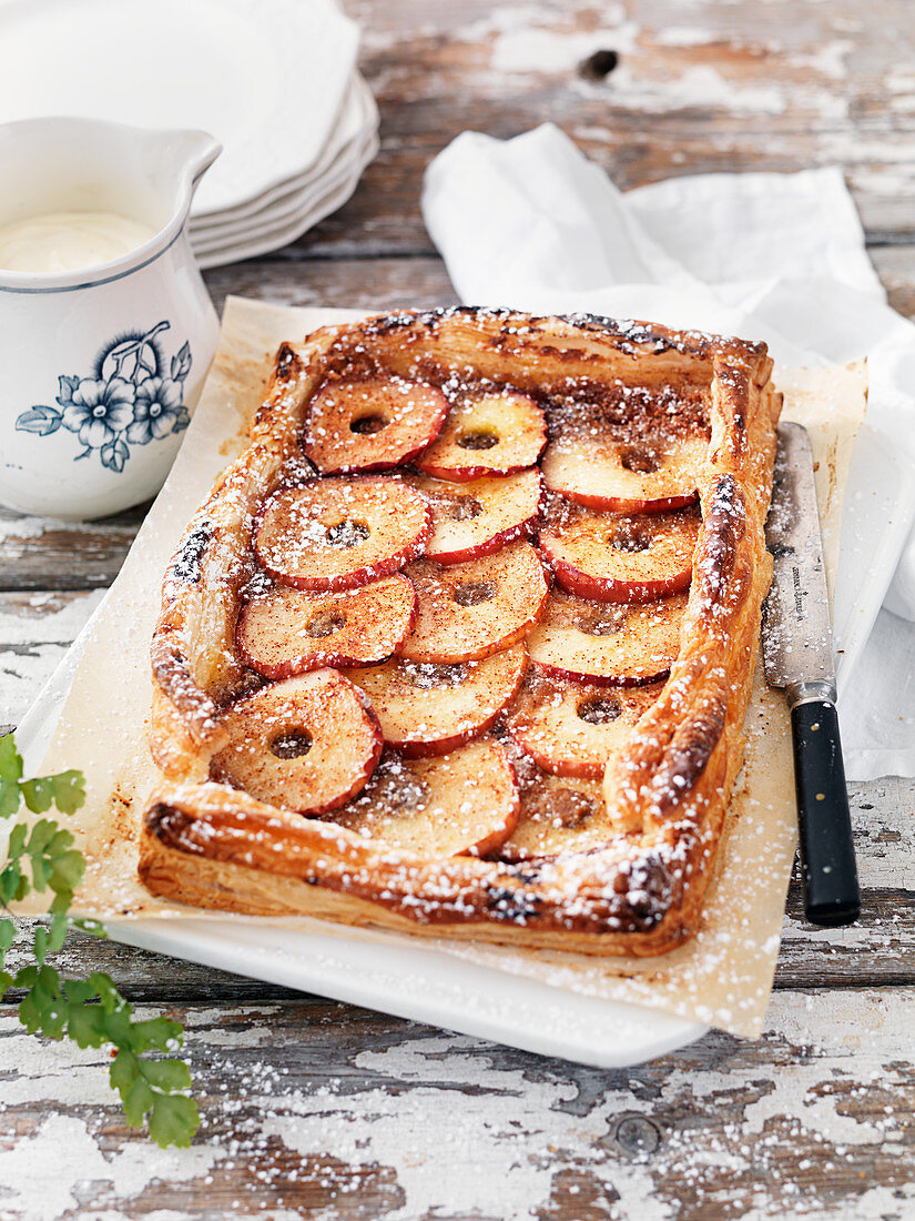 Puff pastry cake with apples, cinnamon, powdered sugar and cream