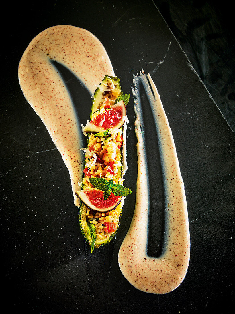Courgette stuffed with bulgur vegetables and figs on tandoori yoghurt