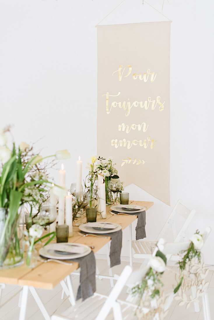 Vase of tulips, dry twigs and pillar candles on table with message on wall in background