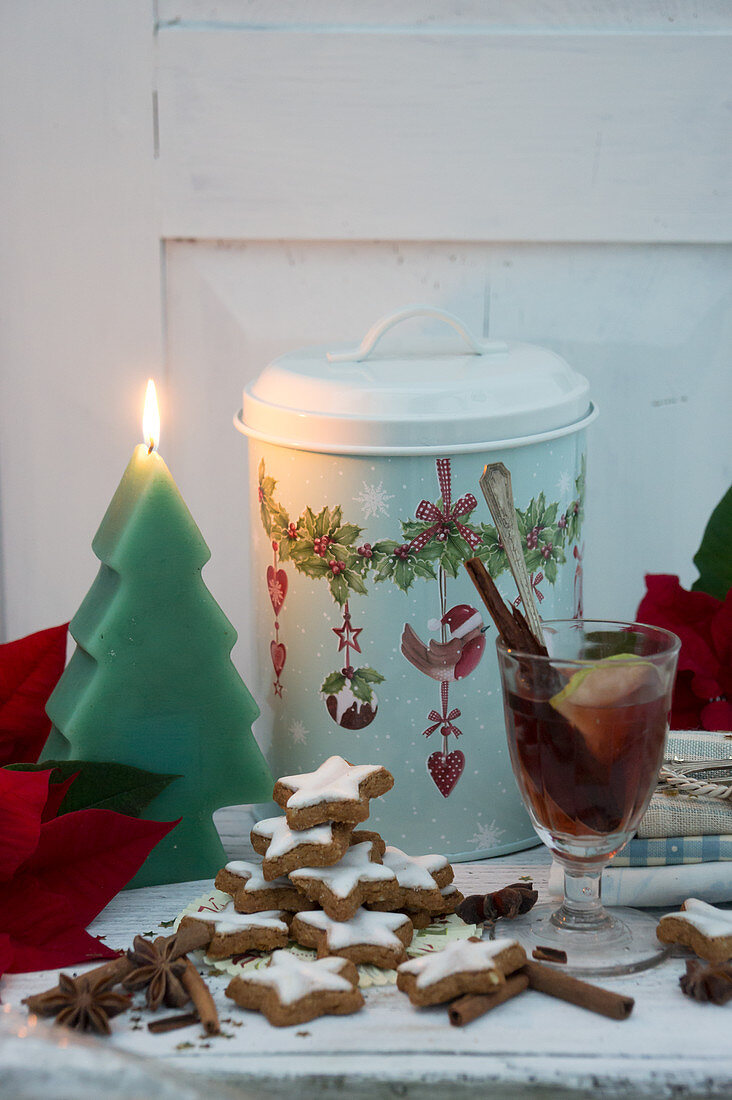 Mulled wine, cinnamon stars, poinsettias, a Christmas tree-shaped candle and a tin